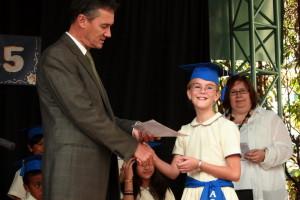 Rektor Jay Long overrekker graduation-diplomet til Birgit. Miss K (Lianne Kalapaca) bak